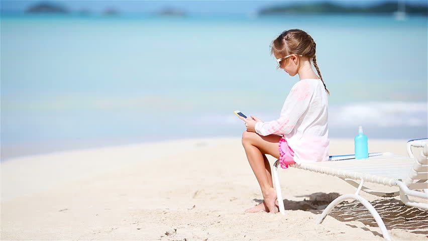 Adorable little girl with smart phone on the sunbed during summer vacation on white beach | Shutterstock HD Video #1013614601