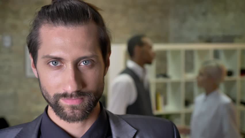 Handsome confident businessman with beard is watching at camera in office, colleagues are talking on background, communication concept | Shutterstock HD Video #1013617031