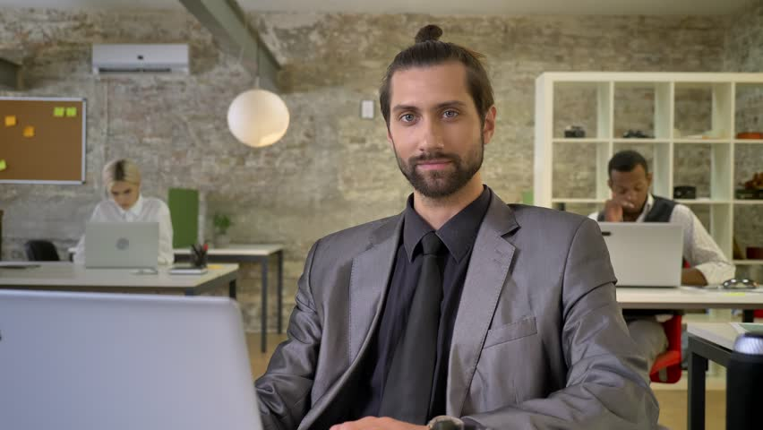 Confident businesswoman with beard is sitting at laptop in office, watching at camera, smiling, colleagues are networking with technologies, work concept, communication concept. | Shutterstock HD Video #1013617121