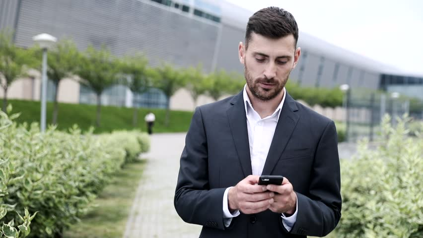 Officially Dressed Young Businessman Standing in the Park. Typing on his Mobile Phone.  | Shutterstock HD Video #1013630771