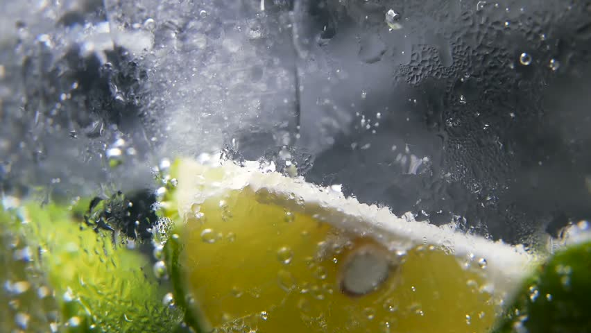 Macro close-up,refreshing soda tonic fizzy water, lime in Glass, ice. Slice of lemon, mineral bubbles. Detox or thirst concept. Healthy, dietary nutrition. Cold lemonade mojito drink. Black background | Shutterstock HD Video #1013636051