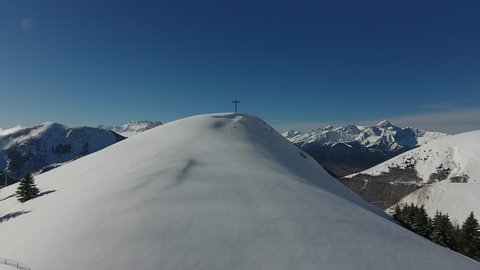 Flying towards a man sitting next to a religious cross on a top of a mountain. Snowy landscape la Salette France. Drone view.