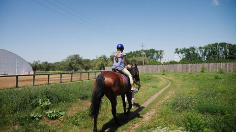 A teenage girl in a protective helmet rides a brown horse on a horse farm. Back view. Slow motion.