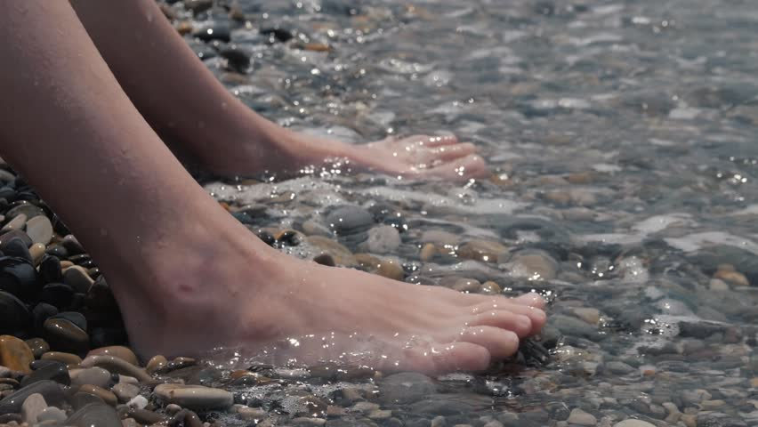 A close-up of a child's legs is overwhelmed by a wave. Pebble sea beach noisy sea waves on children's legs | Shutterstock HD Video #1013679011