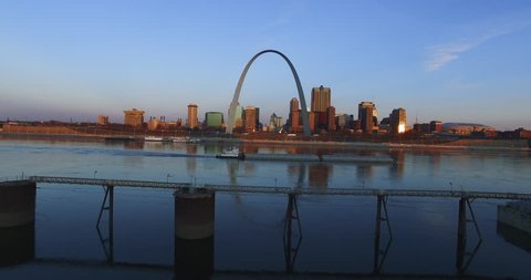 A Barge going down the Mississippi river with St. Louis and the Arch in the background.