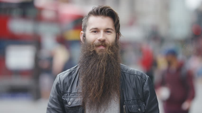 Young man with a long beard smiling to camera and stroking his beard, in slow motion #1013709611