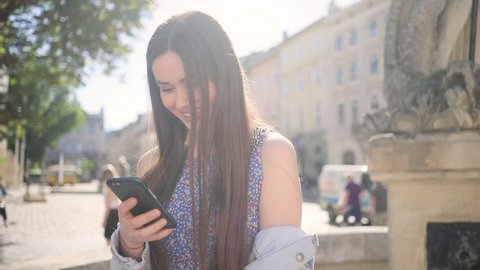 Cute young Caucasian woman with mobile phone in hands waiting for friend in the downtown. Gorgeous smiling Ukrainian girl looking at screen of device. Summer.