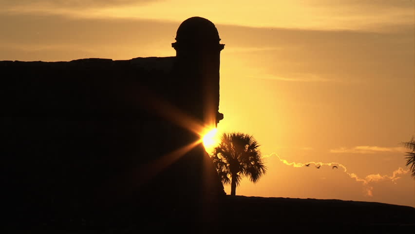 Sunrise behind battlements of historic Castillo de San Marcos (Spanish fort) in St. Augustine Florida. Beautiful sky and sunburst behind silhouetted wall of fort. A flock of birds fly through scene
