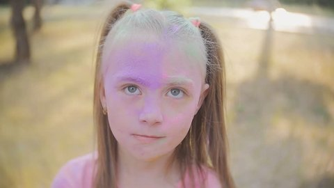 The festival of colors Holi. Portrait of a girl himself showered with colored powder festival of colors Holi