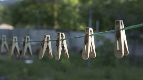 Clothespins hang on a rope on open air summer house