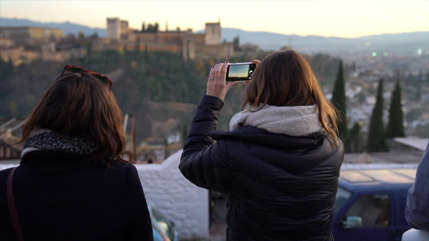 A female tourist takes pictures from a scenic viewpoint of the Alhambra in Granada, Spain.