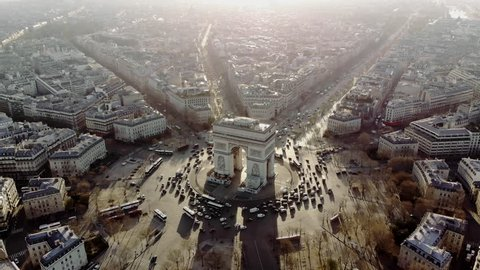 Aerial shot of the Arc de Triomphe and the traffic around it. Cars drive on the Champs Elysees. Paris in morning light.