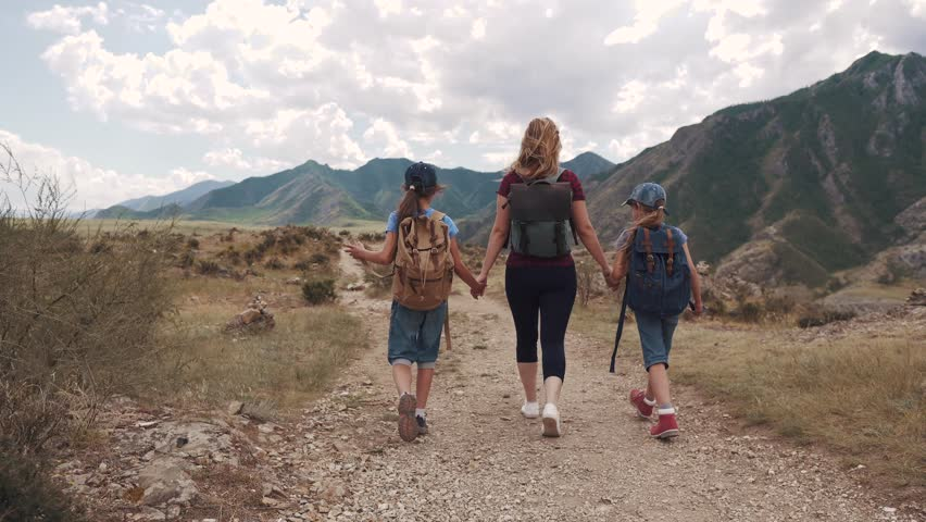 Family of tourists. a young woman with children walking along a path in the mountains. A young mother and children with backpacks go on a hike. back view | Shutterstock HD Video #1013794511