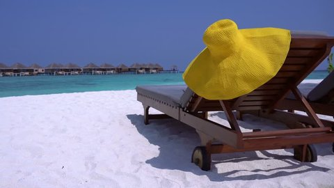 Straw yellow sunhat on wooden sunbed at perfect sandy shore with turquoise sea view, nobody, travel destinations concept