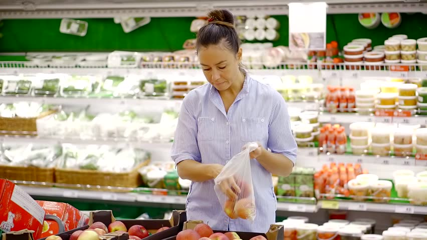 Housewife is taking apples in a grocery department of a supermarket, putting it in plastic package | Shutterstock HD Video #1013819111