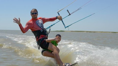 Slow motion. Dad and his son ride on kitesurfing together
