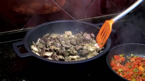 4K, Chef cooking a fresh raw chicken hearts and livers in frying pan. Delicious nutritious organic dietary chicken liver with a high content of protein and iron is actively fried in a stewpan-Dan