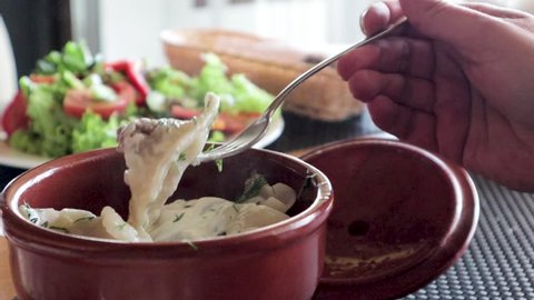 Dumplings in a clay pot. Hot food with steam, salad in the background.