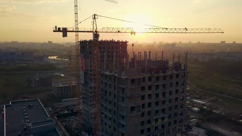 Drone flight under the building construction, the sun shines from behind the building, camera rises up, Russia, Chelyabinsk