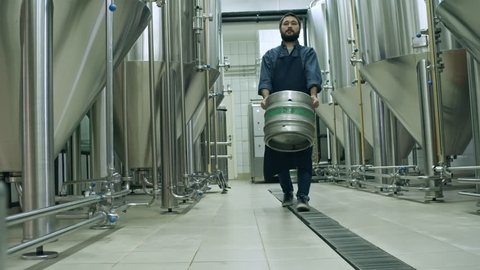 Bearded Asian man in uniform carrying beer keg while walking through brewery towards the camera
