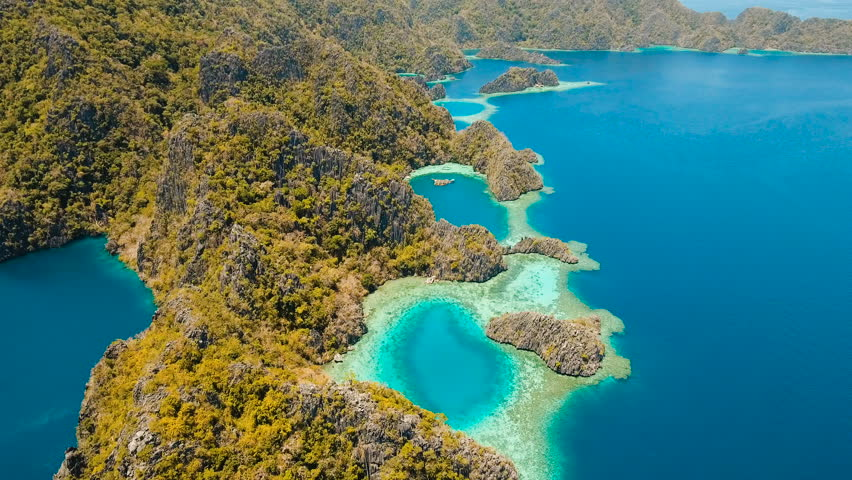 Aerial view: Lagoon with blue, azure water in the middle of small islands and rocks. Beach, tropical island, sea bay and lagoon, mountains with forest, Palawan, Coron. Busuanga. Seascape, tropical
