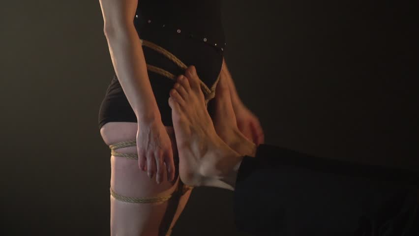 A barefooted man supports a woman on acrobatics, a shibari shooting close-up | Shutterstock HD Video #1013858771