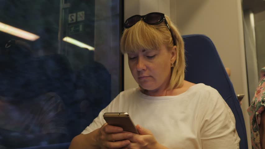 Young beautiful woman tourist traveling by train, sitting next to a window, using a smartphone. The concept of travel | Shutterstock HD Video #1013859821