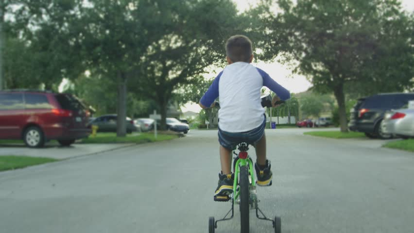 Slow motion from behind of kid riding a bike in a neighborhood street