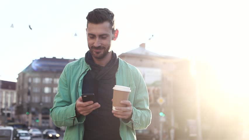 Handsome Bearded Man Walking in the Street at Sunset. Chatting on his Modern Mobile Phone. Drinking Tasty Coffee. Enjoying the Evening Walk. Casually Dressed.Cars, Buses around him. | Shutterstock HD Video #1013876891