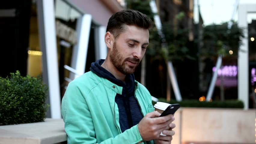 Happily Smiling Bearded Man Standing in the City. Enjoying Time. Chatting on his Mobile Phone with Interest. Typing a Message. Drinking Tasty Coffee. Big Glass Building on the Background. | Shutterstock HD Video #1013880371