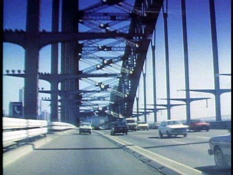 SYDNEY, AUSTRALIA, 1985, POV driving over Sydney Harbor Bridge, traffic on left