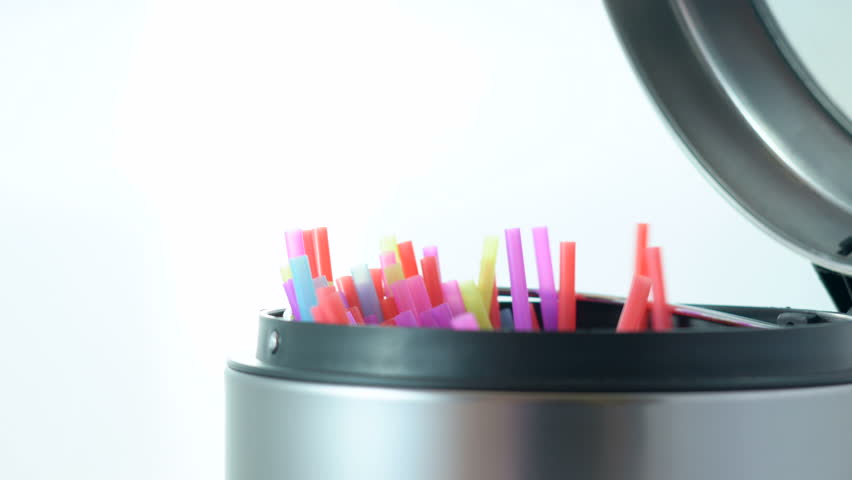Banning plastic straws enviromental concerns concept, throwing straws into trash can close up.