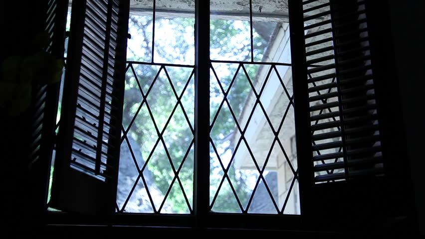 Medium shot of a silhouetted, masked intruder in black as he peers ominously through the window of a house from the outside.