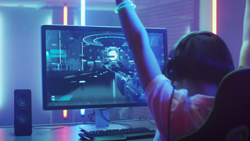 Professional Gamer Playing and Winning in First-Person Shooter Online Video Game on His Personal Computer. He's Talking with His Team Through Headset. Shot on RED EPIC-W 8K Helium Cinema Camera. | Shutterstock HD Video #1013903861