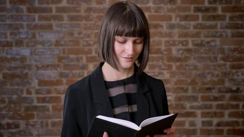 Young concentrated woman with short haircut reading book and standing near brick wall