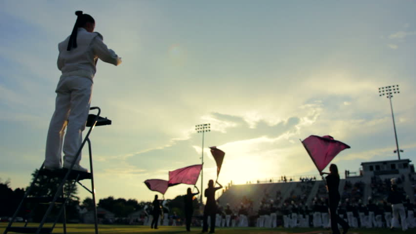 Marching band preforming before a high school football game as the sun sets