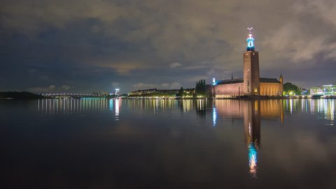 Establishing shot of Stockholm City Hall building at night 4K Time Lapse. Town Hall famous landmark, nobel prize award ceremony. Beautiful calm water reflections, Capital city of Sweden