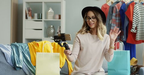 Fashion blogger talking about stylish shopping while making video online on the smartphone with selfie stick. Indoors.