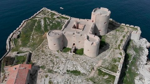 Circling drone shot of Château d'If, famous island of Count of Monte Cristo in France. Flying over French island in the Frioul archipelago in Mediterranean. Historical fortress and prison in France.