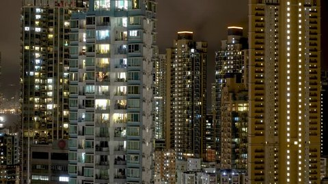 Wide Hong Kong dense apartment buildings timelapse. Chinese crowded city with lights turning on and off at midnight. Fast paced modern Asian night-scape time lapse in urban metropolis.