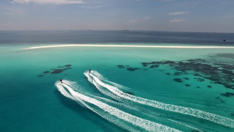 Aerial shot of jet skis heading to a sand bank in the middle of the Indian Ocean