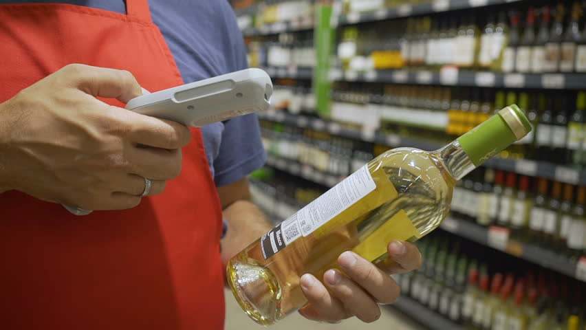 Sales clerk in red aport scanning bottle barcode at wine section in supermarket | Shutterstock HD Video #1013971781