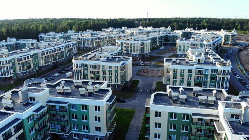 Aerial view on apartment blocks in suburb. Modern residential area in uptown, cars parked along street.
