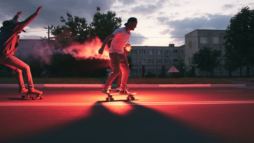 Group of young people skateboarding on the road in the early morning with red signal flare, slow motion
