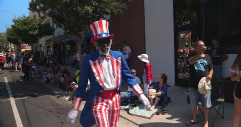 LOS ANGELES, CALIFORNIA, USA - JULY 4, 2018: Afro-american black man dressed as Uncle Sam cheering people at annual Independence Day celebration parade in Santa Monica, Los Angeles, California, 4K