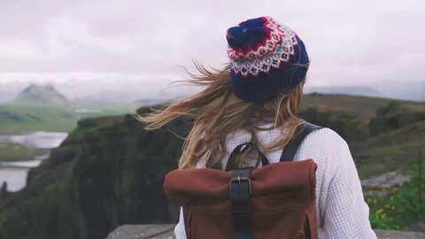 Back view of young attractive girl walking outdoors on background of mountain landscape and ocean, slow motion, close up