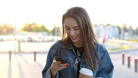 Pretty Young Woman Walking in the City. Using her Mobile Phone. Chatting on it. Typing a Message. Girl Looking Excited, Satisfied. Smiling Happily. Drinking Delicious Coffee. Stylish Outfit.