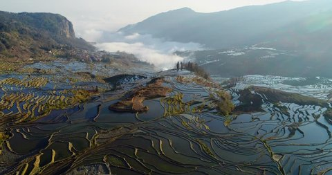 Drone flight over water-filled rice terraces towards a valley covered with dynamic mist. Yuanyang Rice Terraces early in the morning during spring.