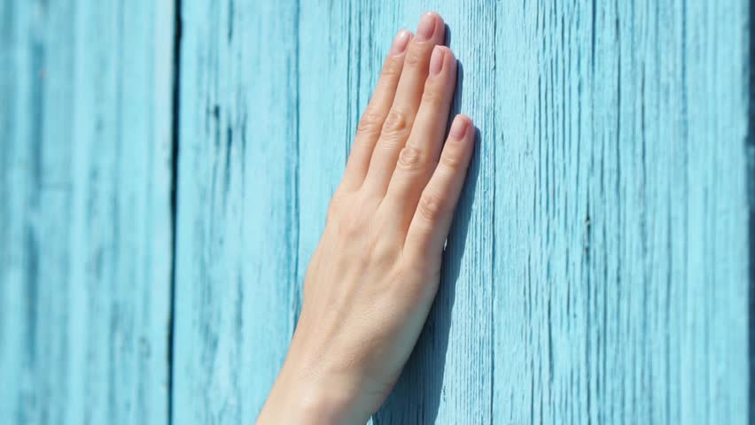 Woman sliding hand against old wooden painted in blue door in slow motion. Female hand touching hard rough surface of blue-colored wood on sunny summer day. Shallow depth of field | Shutterstock HD Video #1014044381