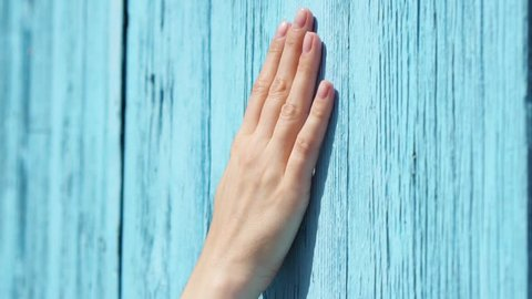 Woman sliding hand against old wooden painted in blue door in slow motion. Female hand touching hard rough surface of blue-colored wood on sunny summer day. Shallow depth of field